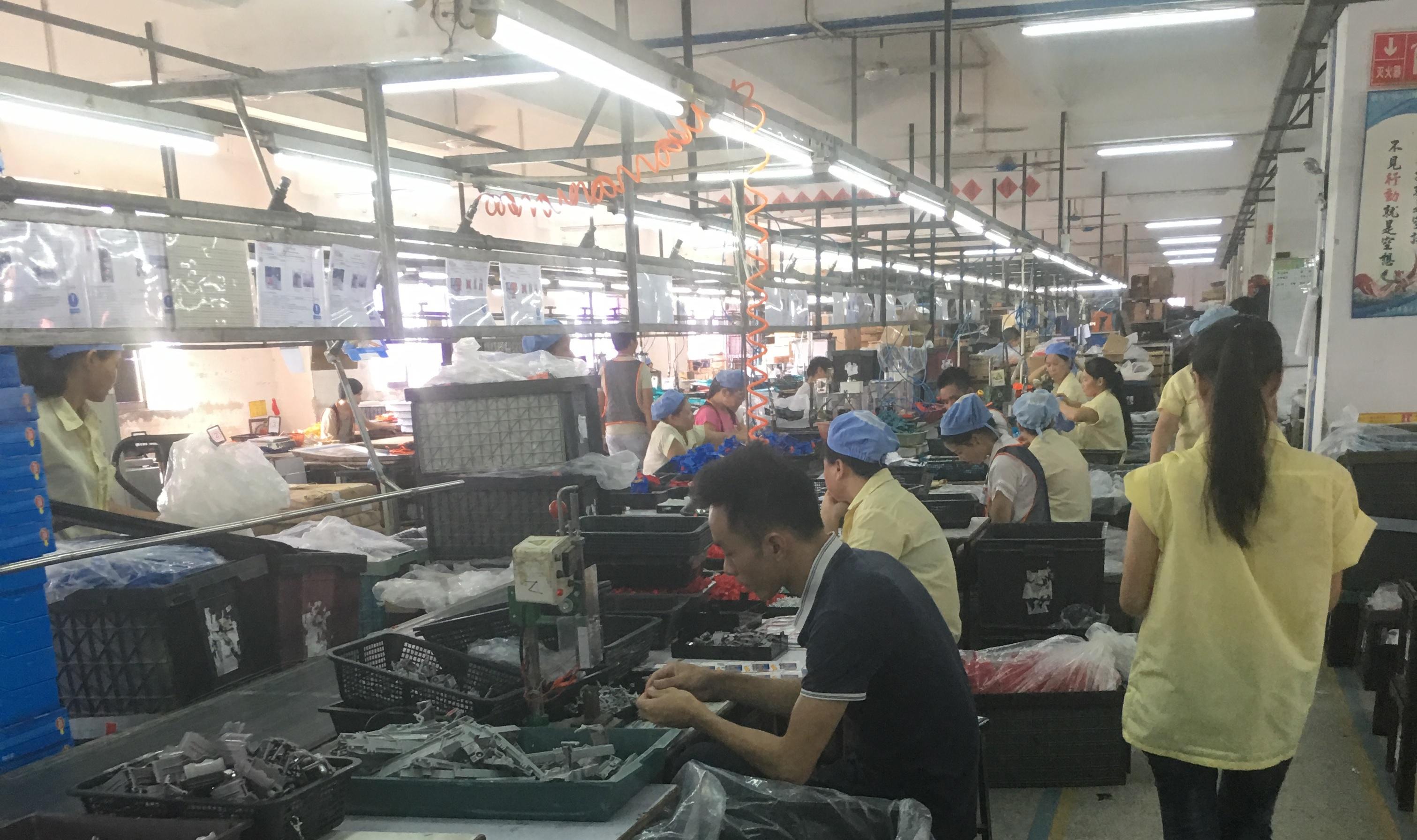 Chinesische Arbeiter*innen arbeiten an einer Produktionslinie für Spielzeugg