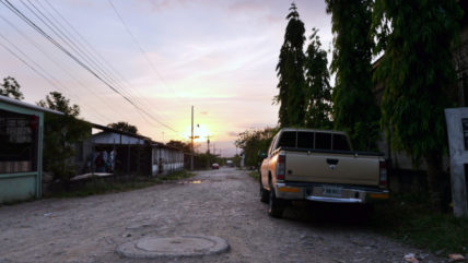Unbefestigte Straße druch ein Dorf südlich von El Progreso, Honduras, in der Abenddämmerung
