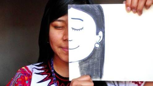 SucelyPuluc hält sich eine Zeichnung ihres Gesichts vor die eine Hälfte ihres Gesichts - eine Kunstperformance mit Hintergrund der Maya Identitätsfindung