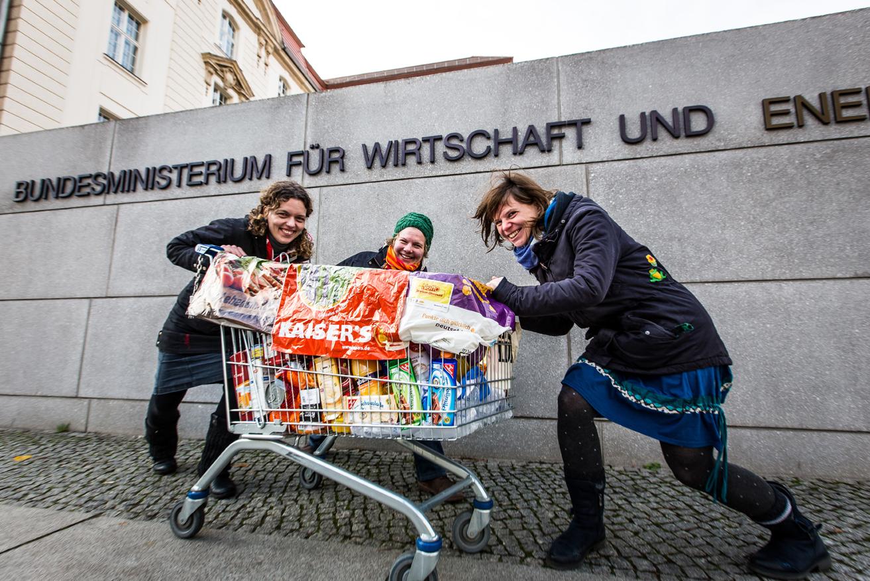 Unser Kampagnenteam kritisiert Einkaufspraktiken von Supermärkten mit einer Aktion vor dem Wirtschaftsministerium in Berlin mit einem bunt gefüllten Einkaufswagen.