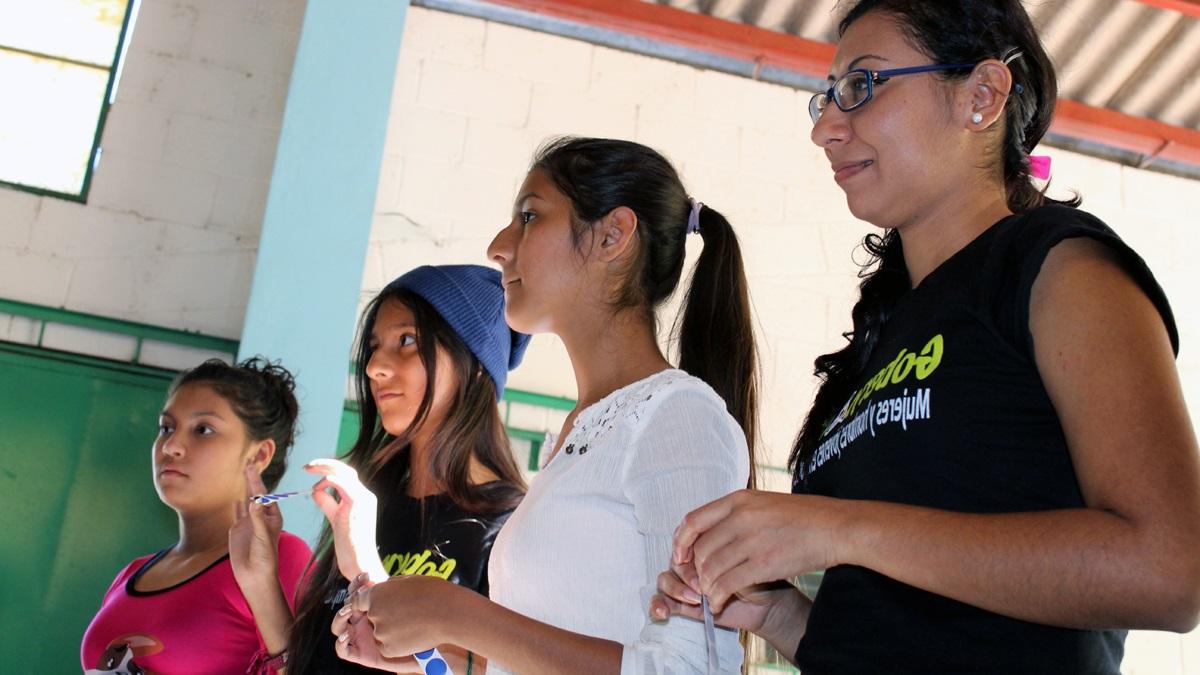 Workshopteilnehmerinnen hören Übungsanleitung zu.