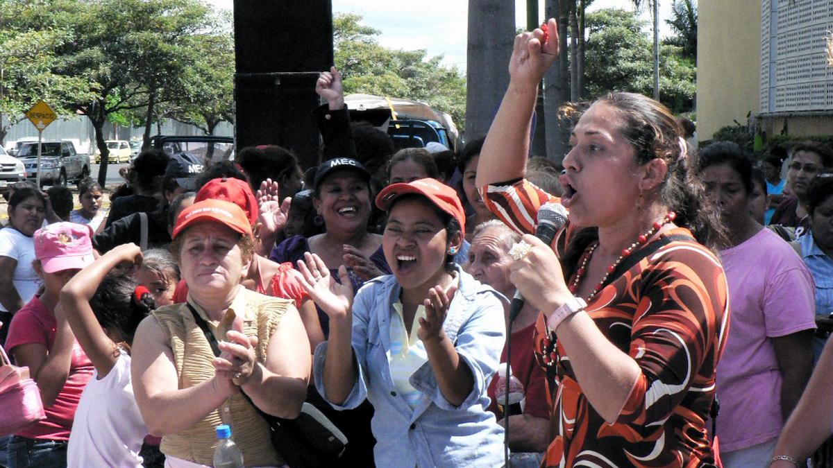 Eine Gruppe von Menschen applaudiert. Eine Frau spricht mit erhobenem Arm ins Mikrophon.