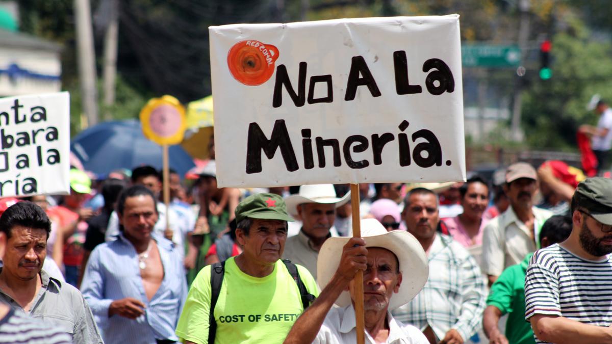 """Teilnehmer einer Demonstration zum Thema Bergbau. Eine Person hält ein Schild mit der Aufschrift """"Gegen Bergbau"""" hoch."""