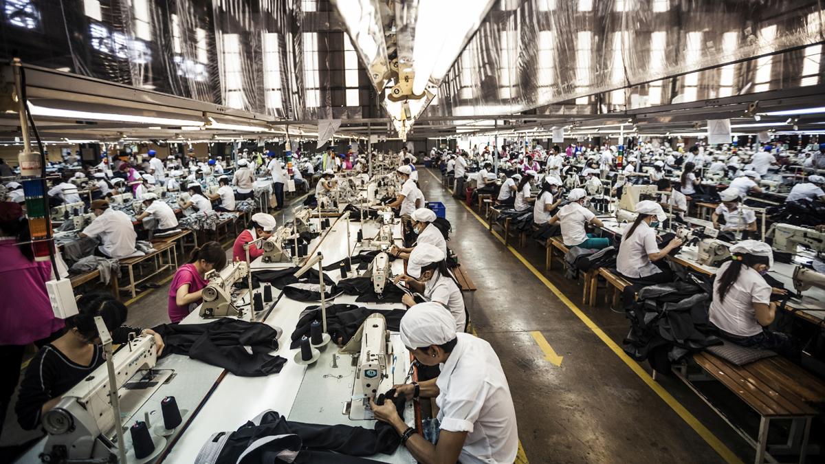 Menschen nähen Kleidung in einer großen Fabrikhalle