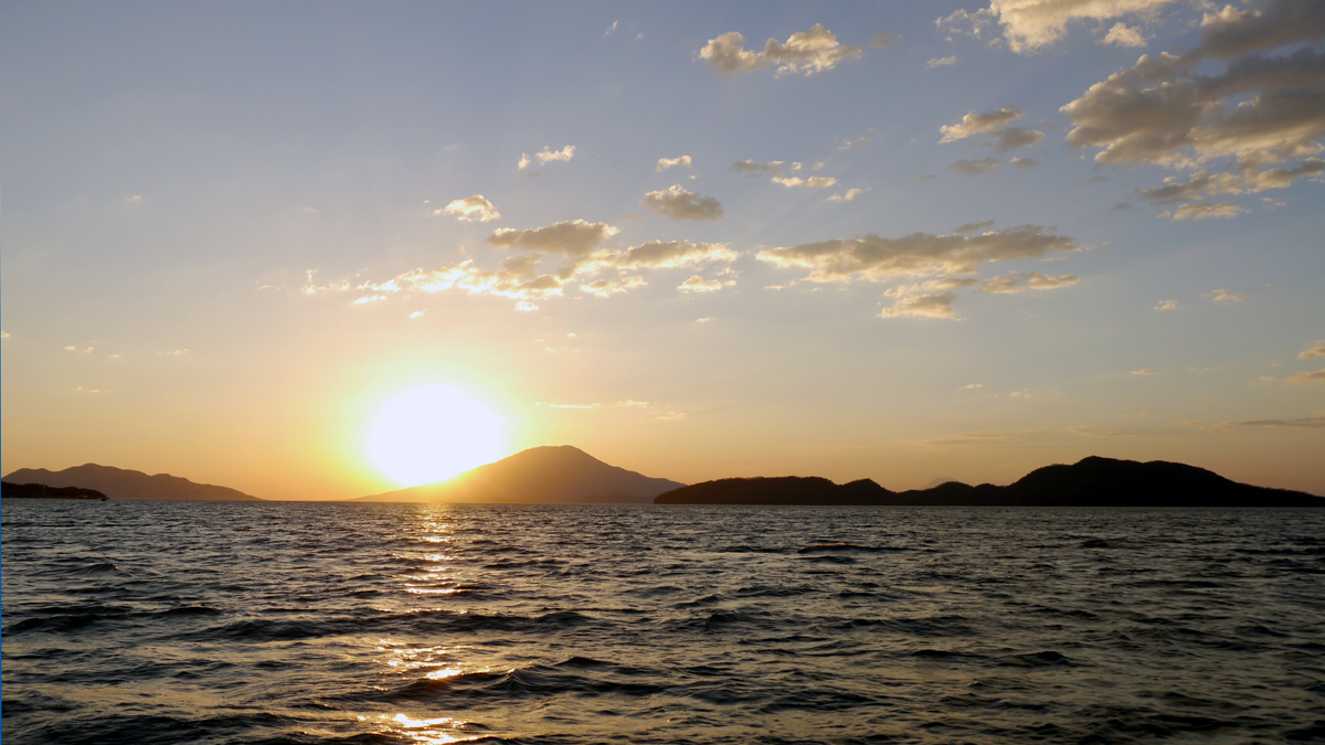 Sonneuntergang hinter einer Insel im Meer