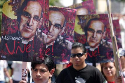 """Demo in El Salvador zum 30. Todestag von Oscar Romero, mehrere Menschen halten Plakate mit """"Romero lebt"""""""