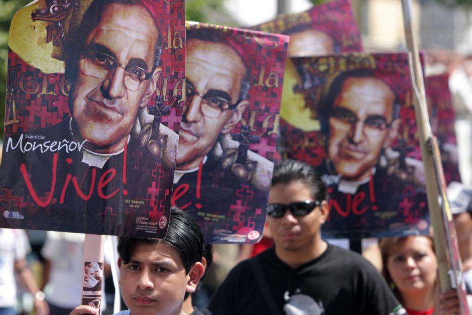 Demo in El Salvador zum 30. Todestag von Oscar Romero, mehrere Menschen halten Plakate mit