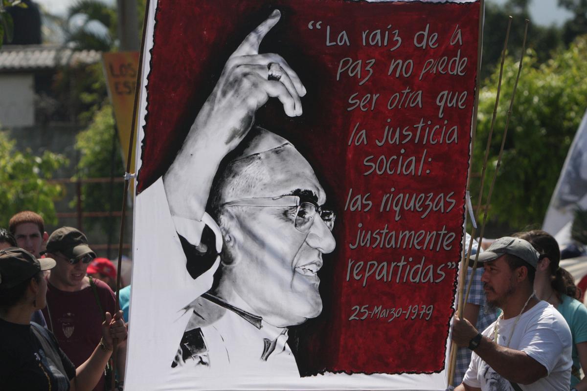 Plakat bei der Demo in El Salvador zum 30. Todestag von Oscar Romero inmitten eines Straßenzugs