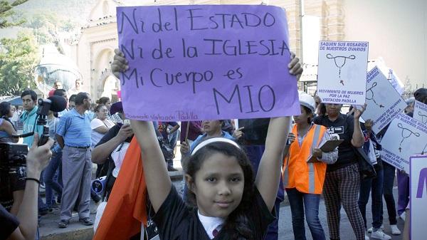 Ein Mädchen hält ein Schild hoch auf dem steht: Dieser Körper gehört weder dem Staat, noch der Kirche, sondern mir.