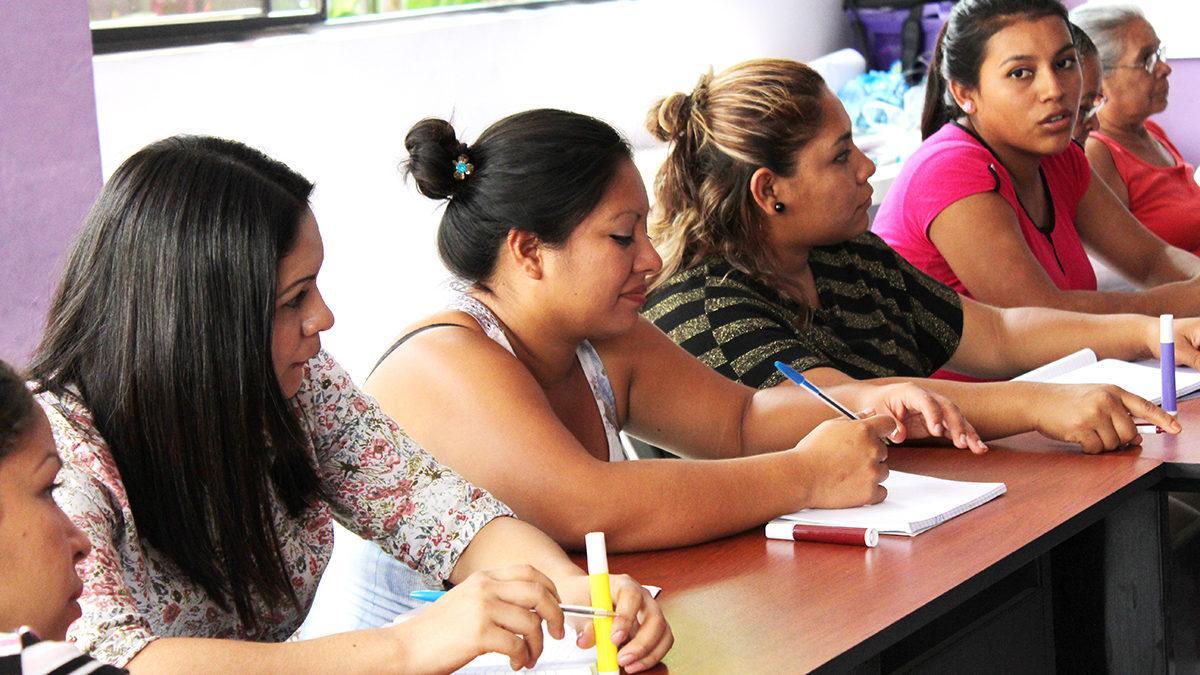Frauen des Maquila Solidaritätsfonds sitzen am Tisch und beraten.