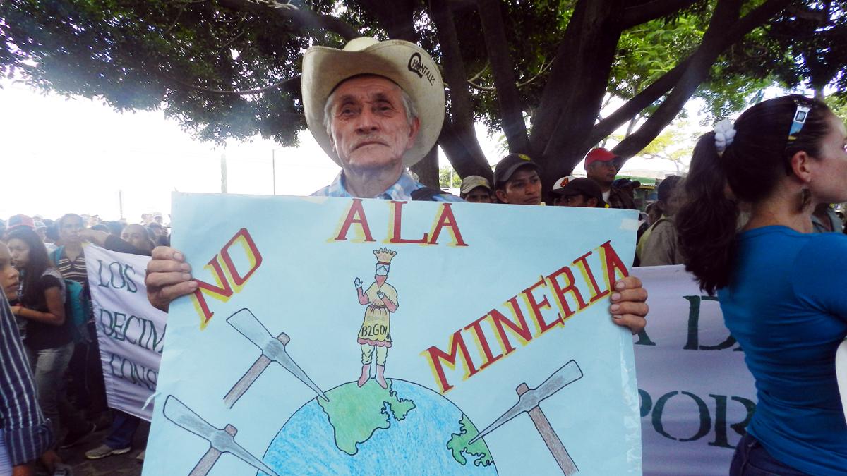 Mann demonstiert mit einem Plakat. Der Slogan darauf lautet: No a la mineria.