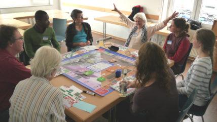 Teilnehmer*innen der Herbsttagung der CIR spielen das Rohstoff-Spiel und diskutieren über 'Imperiale Lebensweise'
