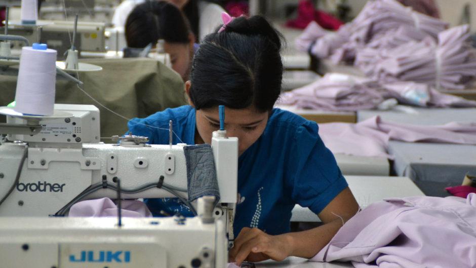 Näherin in einer Fabrik in Myanmar beugt sich über ihre Arbeit