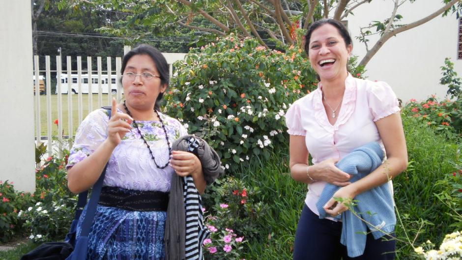 Zwei Teilnehmerinnen der Konferenz gegen Frauenmorde in El Savlador 2010 stehen lachend in einem Garten