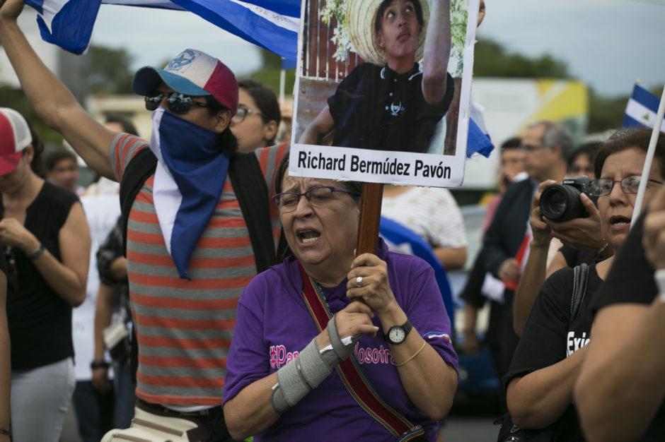 Eine Frau klagt über den Verlust eines jungen Mannes - vielleicht ihr Sohn - dessen Bild sie hochhält. Dahinter eine Menge Demonstrant*innen.
