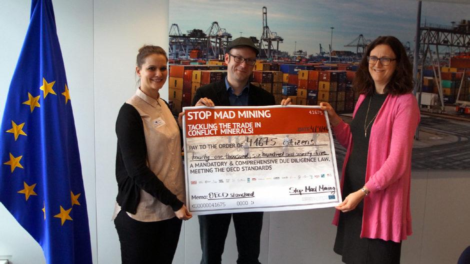 Michael Reckordt und Anna Backmann übergeben eine Petition für eine wirksame Konfliktmieralienverordnung mit über 40.000 Unterschriften als Poster an EU-Handelskommissarin Malmström