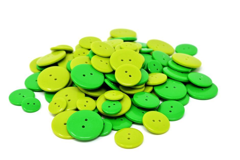 Ein Haufen grüne Knöpfe. Ein grüner Knopf wird dem Siegel als Symbol für ökologische und faire Produktion dienen.