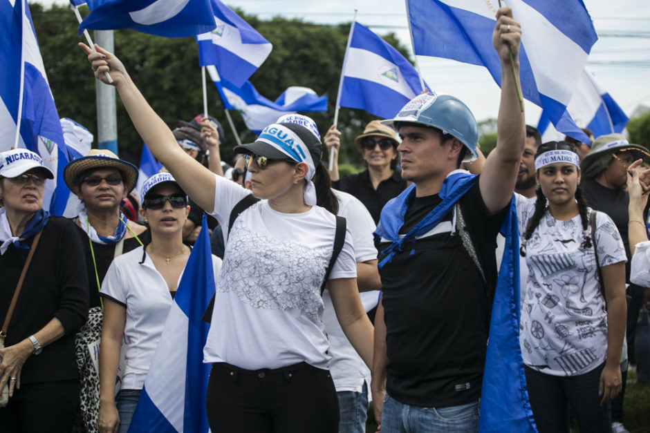 Friedlicher Protest in gedenken an die getöteten Studierenden in Nicaragua, Menchen halten Nicaragua Flaggen hoch