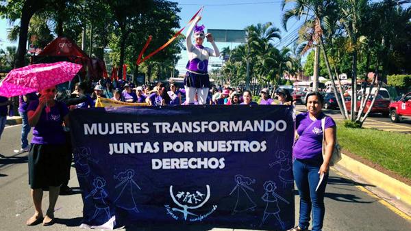 Demonstrationszug mit Mujeres Tranformando Banner und Akrobatin.