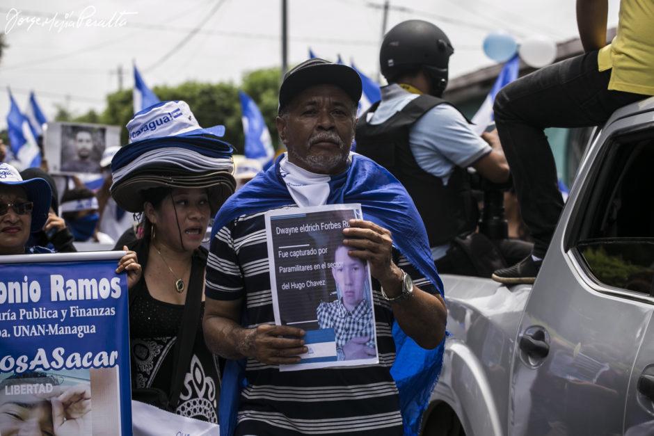 Mann hält Foto eines inhaftierten Aktivisten hoch bei der Demo 'Wir sind eine Stimme'