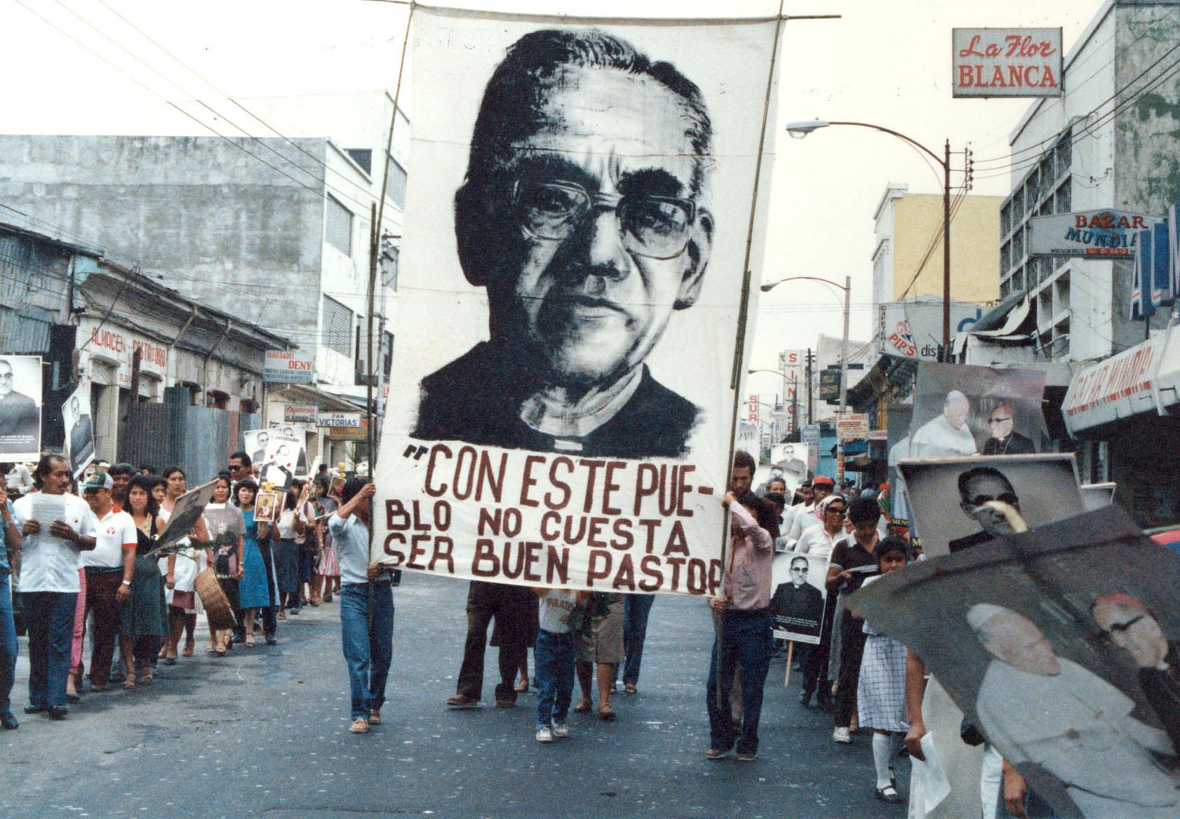 """In Gedenken an Oscar Romero trägt ein Demonstrationszug sein Konterfei mit dem Zitat """"Mit so einem Volk ist es nicht schwer, ein guter Hirte zu sein"""" durch eine Straße in El Salvador."""