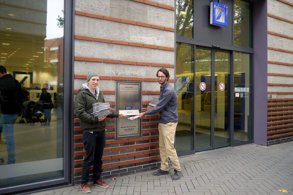 CIR-Referenten Christian Wimberger und Patrick Niemann mit den gesammelten Protespostkarten vor einer Filiale der Deutschen Bank