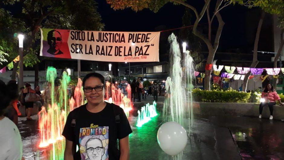 Dotothee Mölders vor einem Springbrunnen, über dem ein Banner mit dem Porträt Oscar Romeros hängt