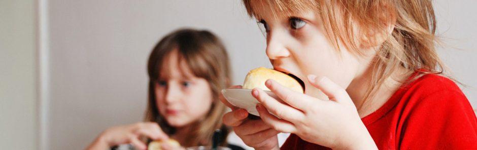 Zwei Kinder essen Gebäck