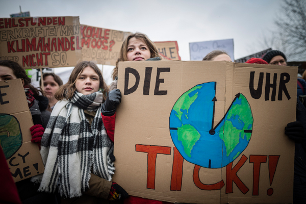 Mehrere FridaysForFuture Demonstrant*innen halten Plakate, unter anderem eines mit einer Weltkugel als Uhr und dem Schriftzug