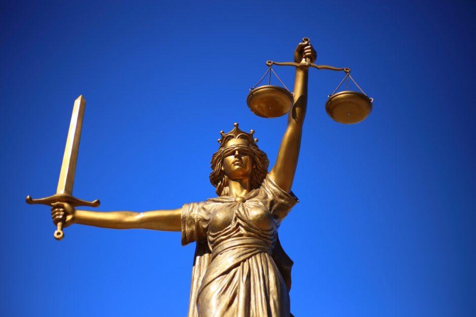 Justitia in Gold vor blauem Himmel