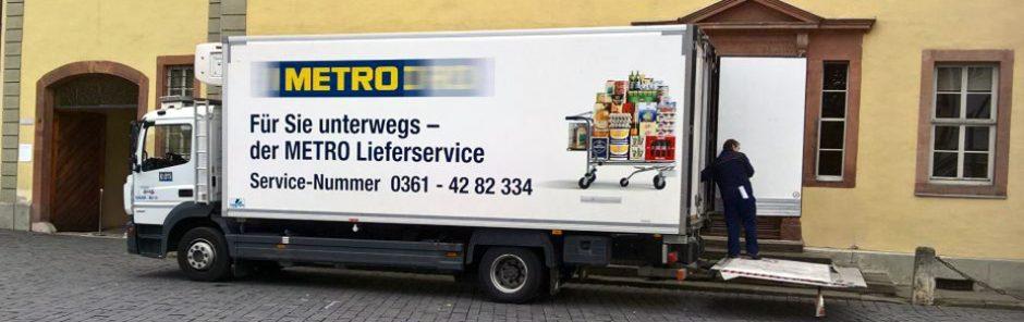 LKW von Metro Großhandel wird entladen, auf dem LKW ist ein voll beladener Einkaufswagen abgedruckt