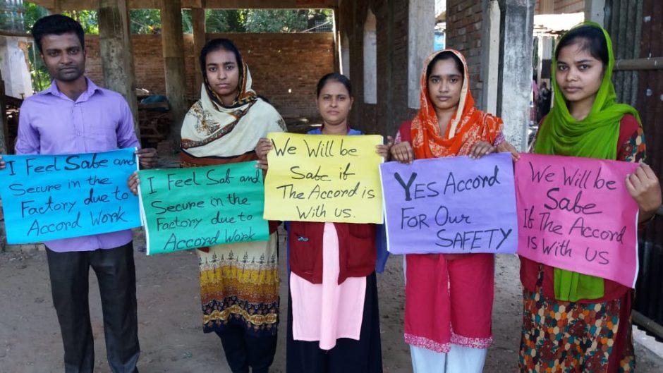 Arbeiter und Arbeiterinnen aus Bangladesch halten bunte Plakate, auf denen u.a. steht
