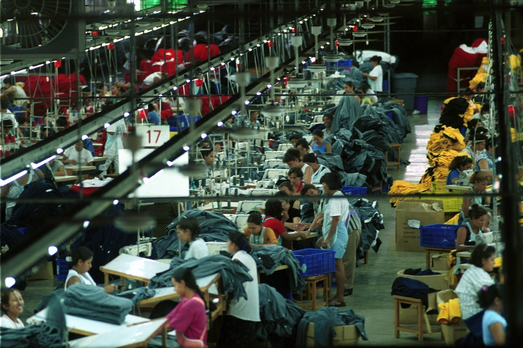 Einblick in eine Nähfabrik, in der Arbeteir*innen Tisch an Tisch Kleidung fertigen