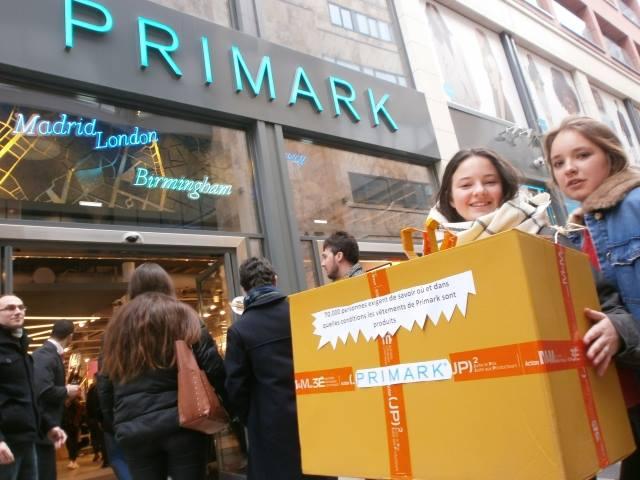 Zwei Aktivistinnen stehem mit einer großen Geschenkbox vor dem Eingang einer Primark Filiale