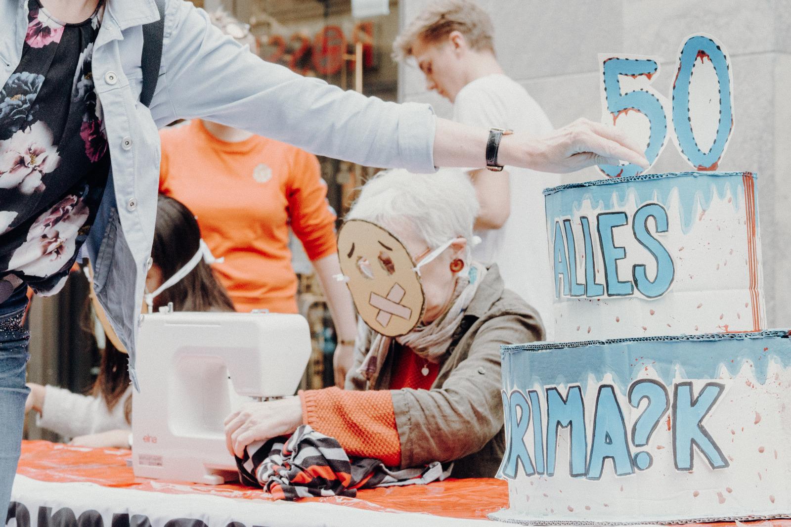Passantin wirft eine Aktionspostkarte an Primark in eine Box in Form einer Geburtstagstorte. Im Hintergrund das Straßentheater vor dem Primark Münster
