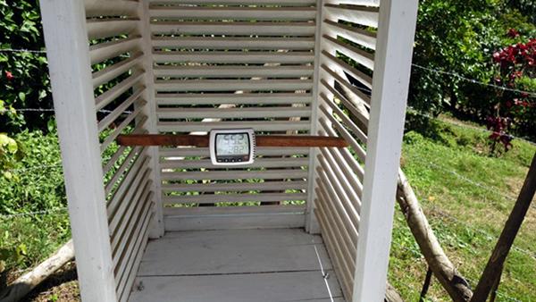 Eine Kasten aus weißen Holzlamellen umgibt die Messaparatur der Klimastation.