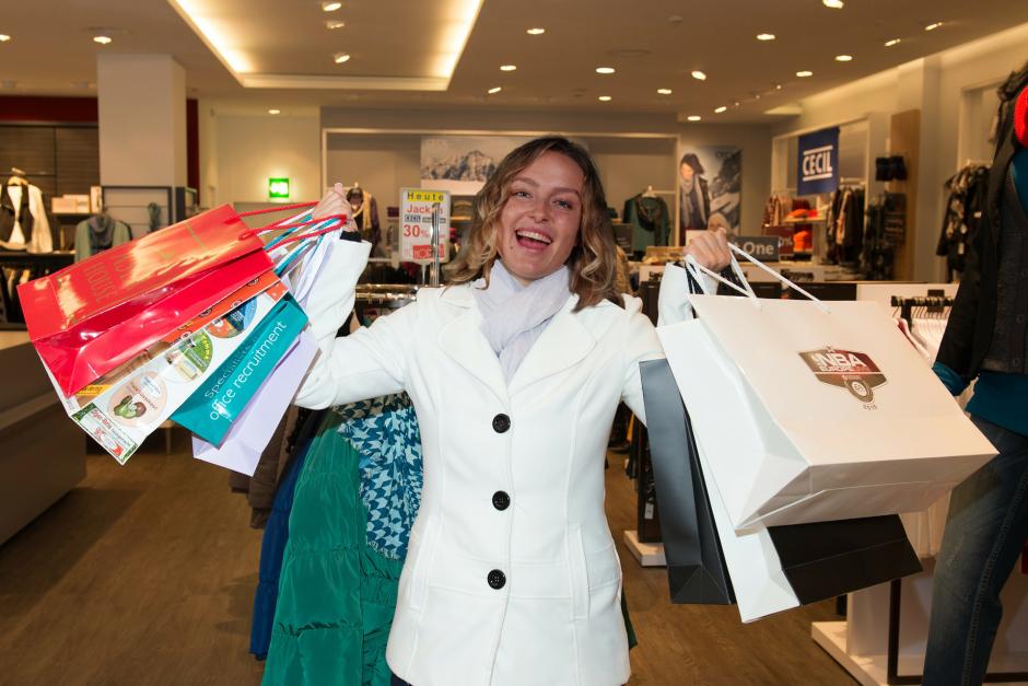 Das Bild zeigt Carolin als Shopaholic, wie sie strahlend viele Einkaufstüten hochhält