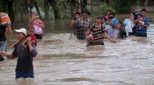Menschen waten durch Hüfthohe, braune Wassermassen und tragen Hab und Gut und Kinder.
