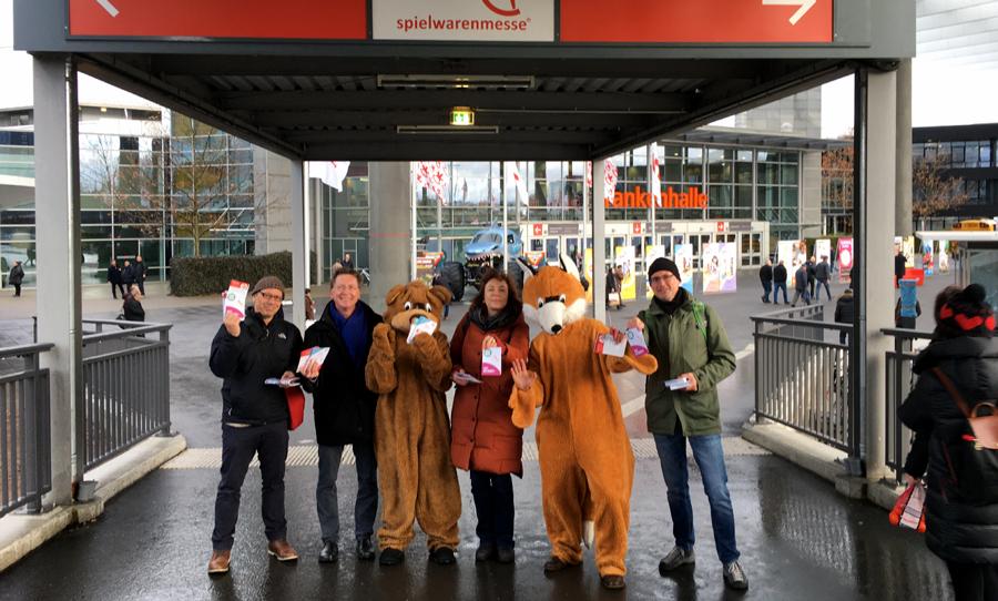 Vor dem Eingang der Nürnberger Spielwarenmesse weisen sechs Mitglieder des Nürnberger Bündnis Fair Toys auf die Bedeutung von würdigen Arbeitsbedingungen in der Spielzeugproduktion hin.