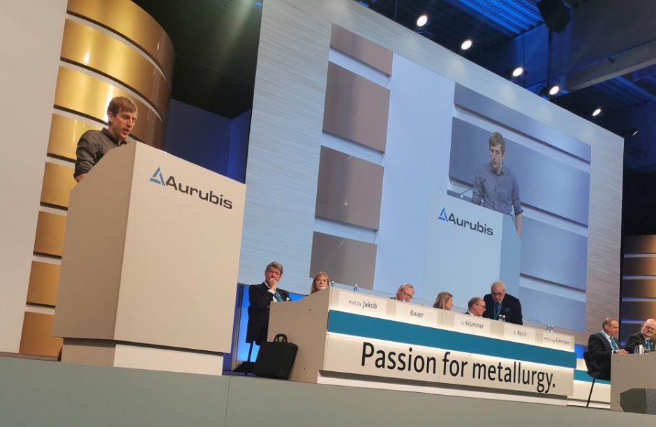 CIR-Referent Christian Wimberger steht auf dem Podium und hält eine Rede, links daneben sitzen die Aufsichtsräte und Vörstände von Aurubis, darüber eine große Leinwand, auf der der Referent nochmal zu sehen ist.