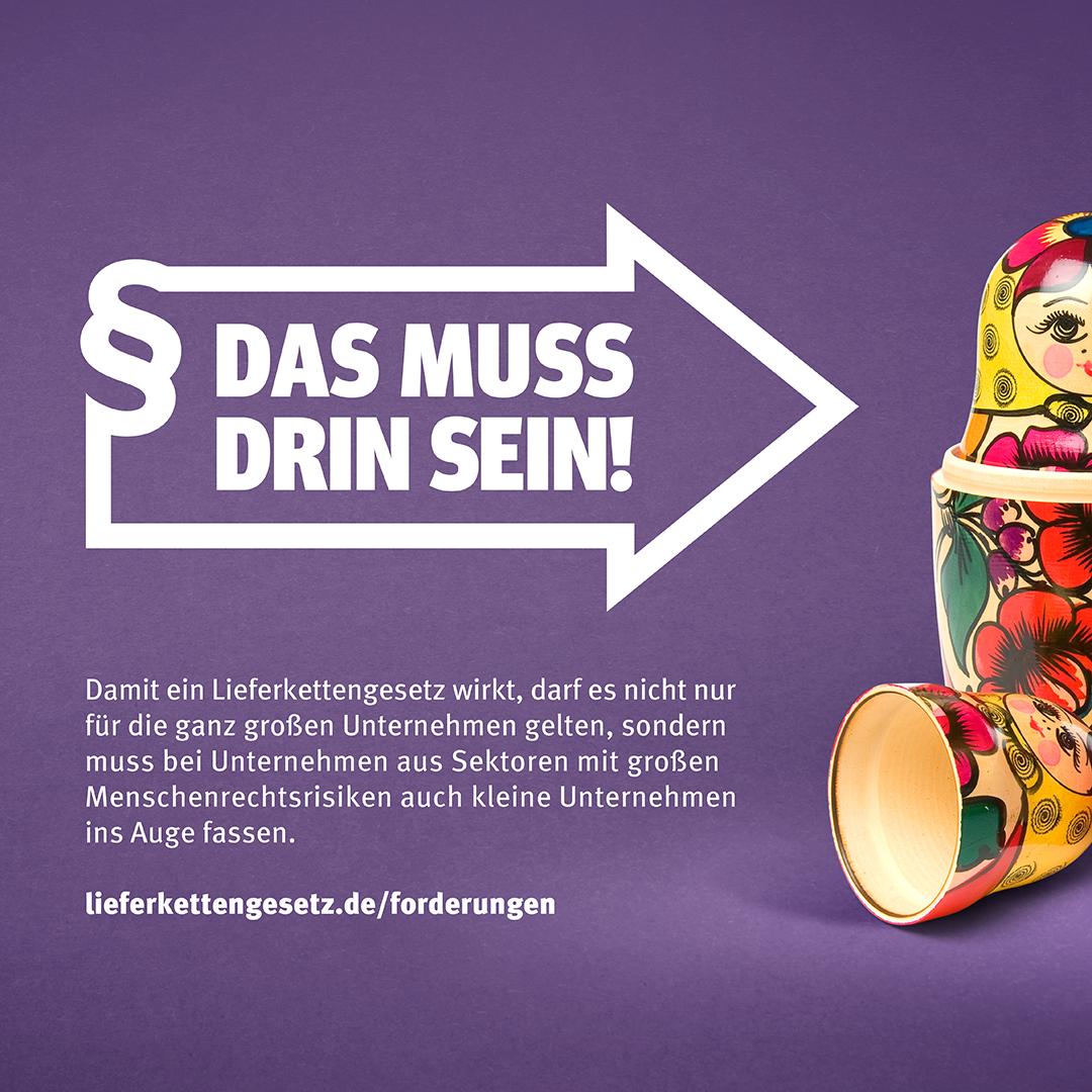 """Pfeil im Stil des Logos der Initiative Lieferkettengesetz mit den Spruch """"Das muss drin sein!"""" zeigt auf eine Babuschka-Holzpuppe"""
