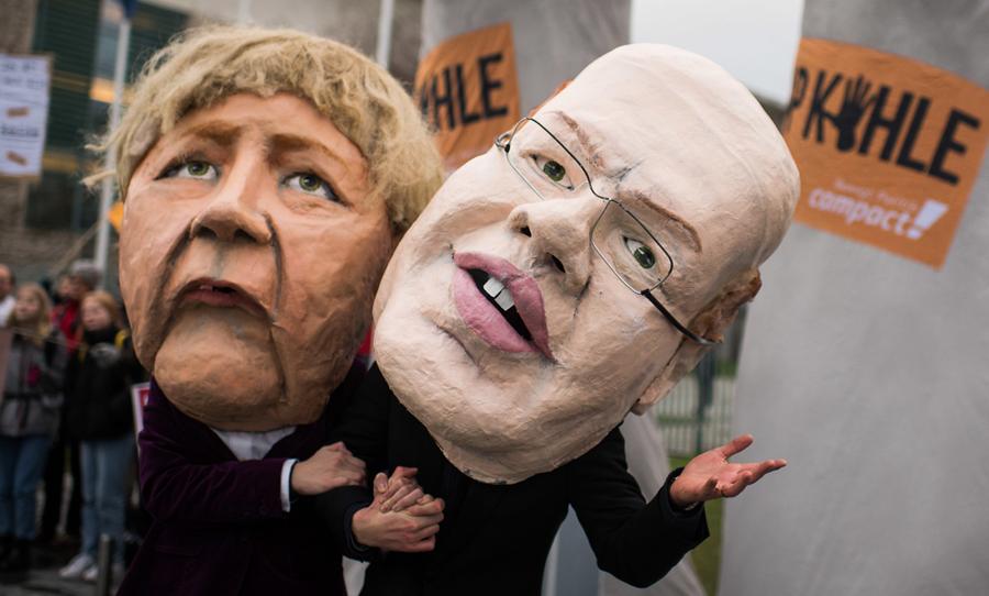 2 Menschen in schwarzen Anzügen mit überdimensionalen Pappmachée Köpfen von Bundeskanzlerin Angela Merkel und Bundeswirtschaftsminister Peter Altmaier