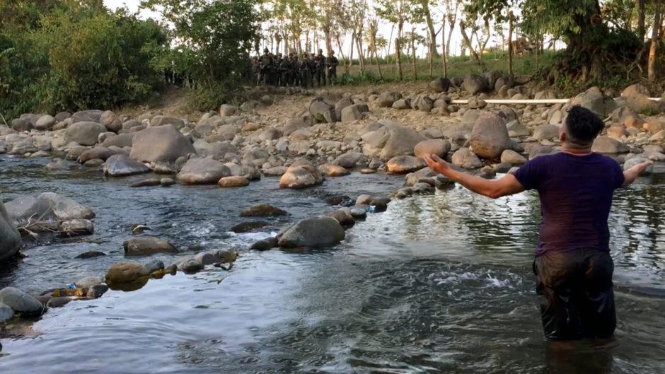 Aktivist steht im Fluss Guapinol und breitet die Arme aus richtung einer bewaffneten Truppe Sicherheitskräfte in Uniform am anderen Ufer.