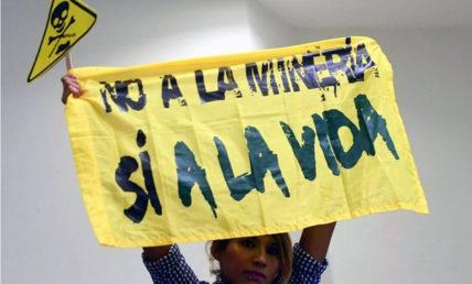 """Mensch hält ein gelbes Banner hoch mit der schwarzen Aufschrift """"Nein zum bergbau, ja zum Leben"""" (auf Spanisch)"""