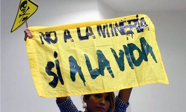 Mensch hält ein gelbes Banner hoch mit der schwarzen Aufschrift