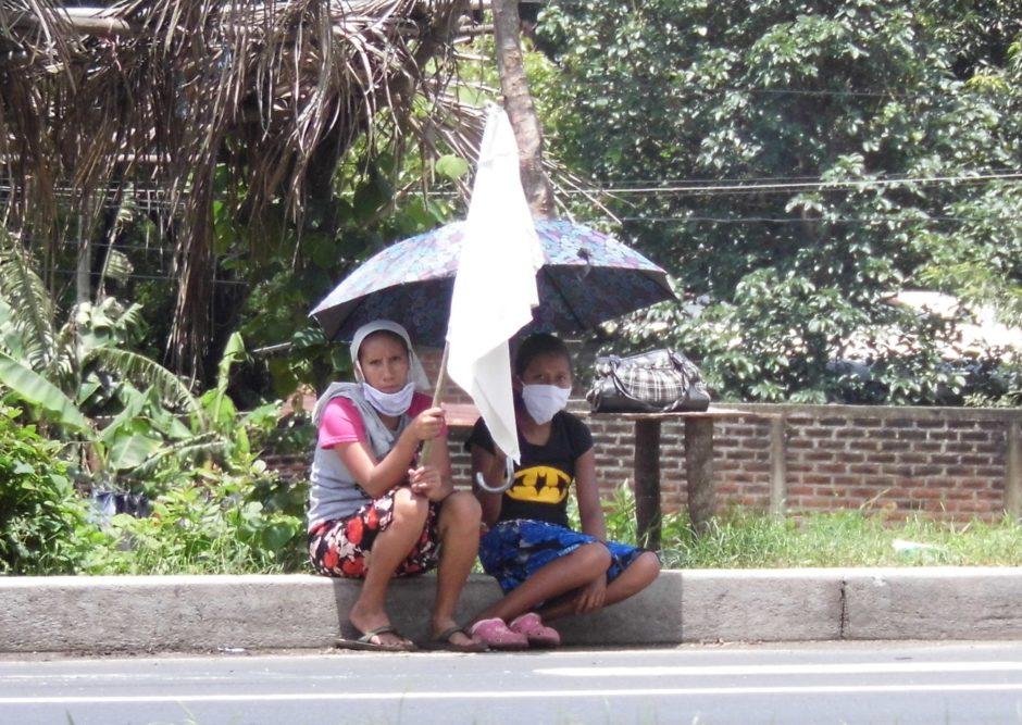 Zwei Menschen sitzen in El Salvador mit einer weißen Fahne in der Hand am Straßenrand