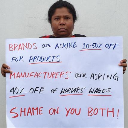 Aktivistin mit Schild protestiert gegen Lohnkürzungen