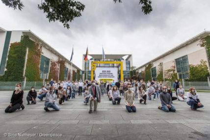 Aktivist*innen knien vor einem symbolischen gesetzlichen Rahmen in Berlin