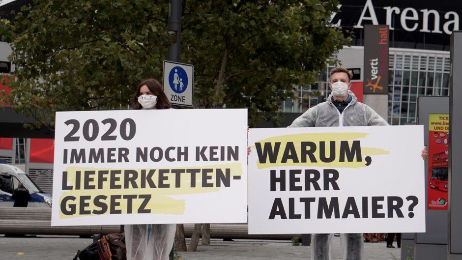 Aktivist*innen der Initiative Lieferkettengesetz protestieren beim Tag der Deutschen Industrie mit Plaketen.