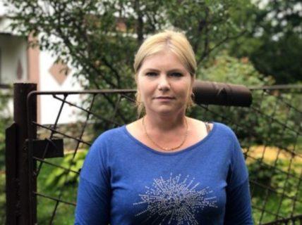 Näherin Angelica Manole steht vor einem Gartenzaun